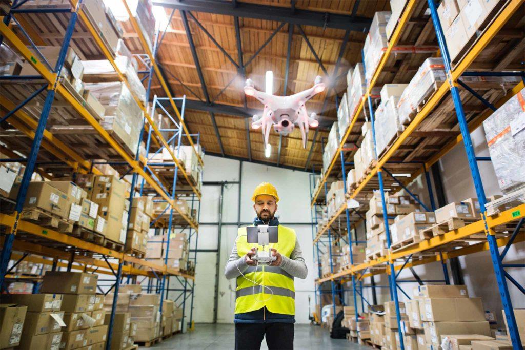 Mann bedient eine Drohne in einem Warenlager