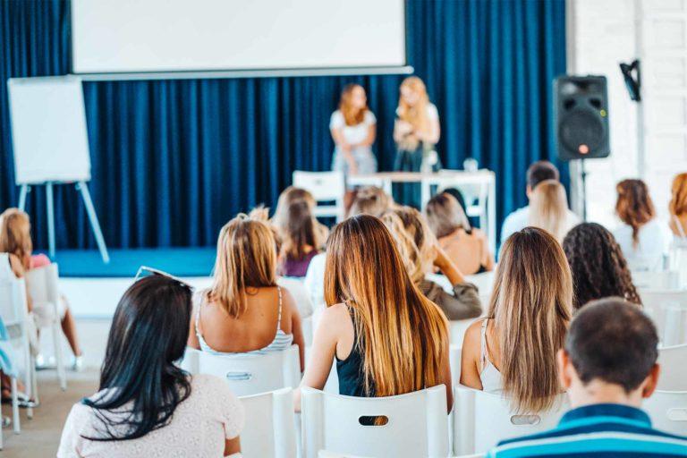Mehrere Personen hören zwei Gründerinnen bei einem Vortrag zu