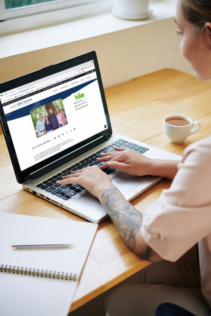 Junge Frau liest am MacBook einen Beitrag auf der Webseite von HARZ Startups